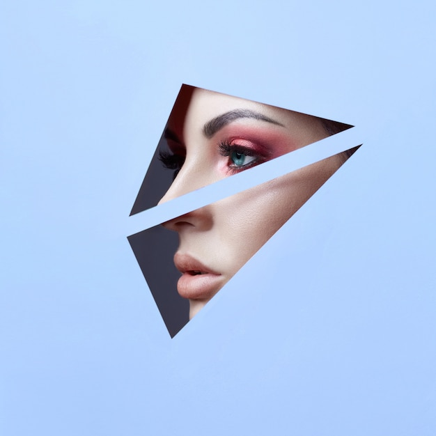 Schoonheid gezicht rode make-up ogen van een jonge vrouw in een spleet gat van blauw papier. vrouw met mooie make-up rode gloeiende schaduw, grote blauwe ogen in het spleetgat. advertentie kopie ruimte Premium Foto