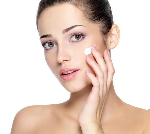 Schoonheid gezicht van jonge vrouw met cosmetische crème op een wang. huid zorg concept. closeup portret geïsoleerd op wit. Gratis Foto