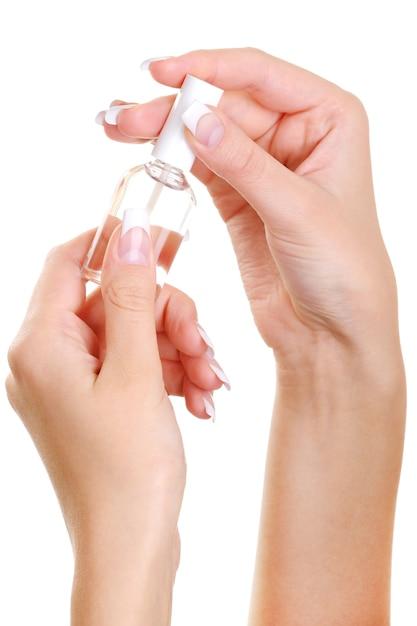 Schoonheid goed verzorgde vrouwelijke hand houdt het flesje van een nagel verdwijnen Gratis Foto