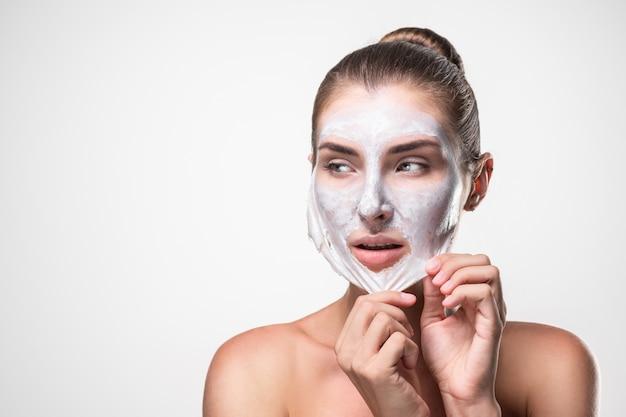 Schoonheid huidverzorging cosmetica en gezondheidsconcept. jonge vrouw gezicht, vrouw gezichtsschil verwijderen van masker. Premium Foto