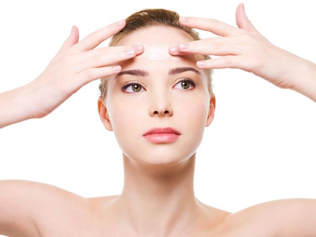 Schoonheid kaukasische jonge vrouw moisturizer crème op het voorhoofd toe te passen - geïsoleerd op wit Gratis Foto