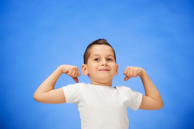 Schoonheid lachende sport kind jongen toont zijn biceps Gratis Foto