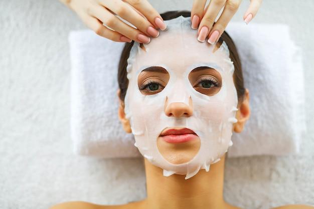 Schoonheid. mooie vrouw in de schoonheidssalon met gezichtsmasker. liggend op de massagetafels. zuivere en frisse huid. huidsverzorging. hoge resolutie Premium Foto