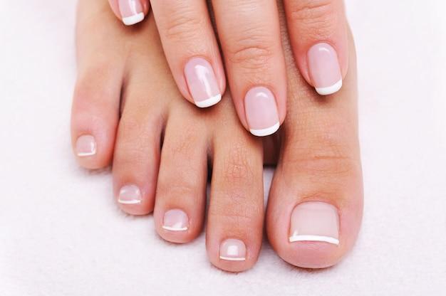 Schoonheid nagels concept van een vrouwelijke hand en voeten met prachtige franse manicure en pedicure Gratis Foto