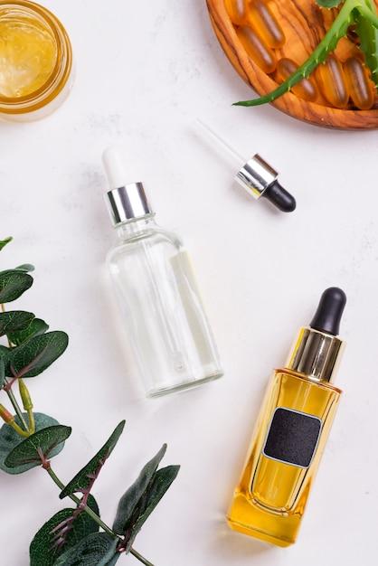Schoonheid natuurlijke producten met cosmetische crème, omega 3 gel capsules en serum in glazen flessen op wit Premium Foto