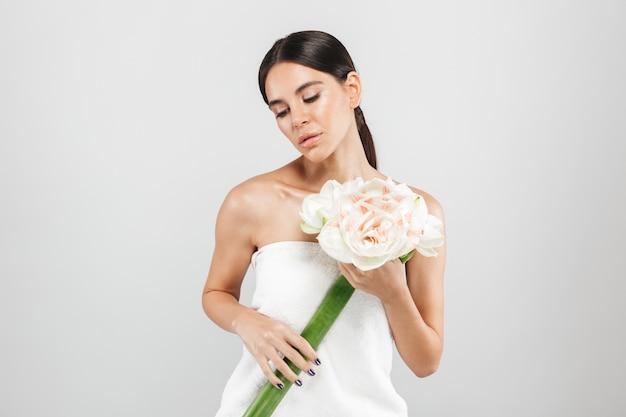 Schoonheid portret van een aantrekkelijke sensuele gezonde vrouw geïsoleerd over witte muur, poseren met een bloem Premium Foto