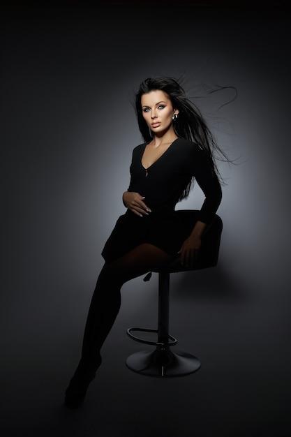 Schoonheid portret van een brunette vrouw met haar in de wind vliegen. professionele make-up, perfect gezicht van een sexy vrouw Premium Foto