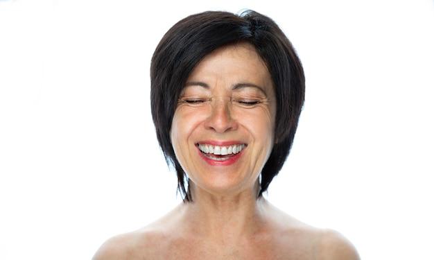 Schoonheid portret van een senior vrouw lachen op een witte achtergrond Premium Foto