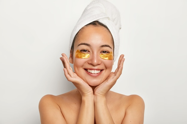 Schoonheid portret van gelukkig aziatisch meisje houdt palmen in de buurt van gezicht, ziet er positief uit, toont witte perfecte tanden, geniet van spa-procedures, staat met gewikkelde handdoek op het hoofd Gratis Foto
