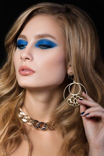 Schoonheid portret van jonge blonde vrouw met blauwe smokey eyes make-up dragen van gouden sieraden en haar oorbel aan te raken. mode make-up. Premium Foto