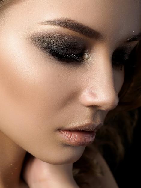 Schoonheid portret van jonge vrouw met gouden make-up. perfecte huid- en modemake-up met gouden accenten. Premium Foto
