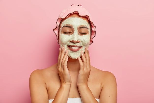 Schoonheid shot van lachende jonge etnische meisje past een hydraterend masker toe op het gezicht, ondergaat een gezichtsbehandeling binnen, staat met blote schouders, draagt een roze douchemuts op het hoofd Gratis Foto