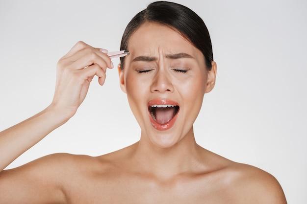 Schoonheid van beklemtoonde jonge vrouw met bruin haar die in pijn gillen terwijl het plukken van wenkbrauwen die pincet met behulp van, dat over wit wordt geïsoleerd Gratis Foto