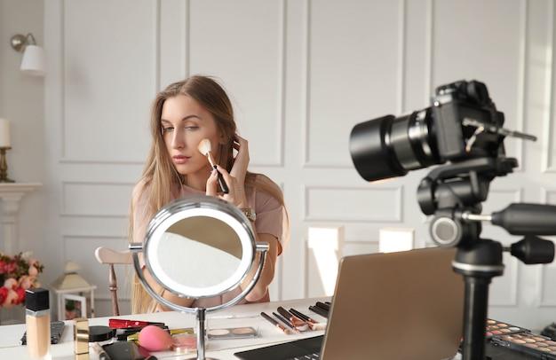 Schoonheid vlogger. jonge vrouw die een make-uptutorial opneemt Gratis Foto