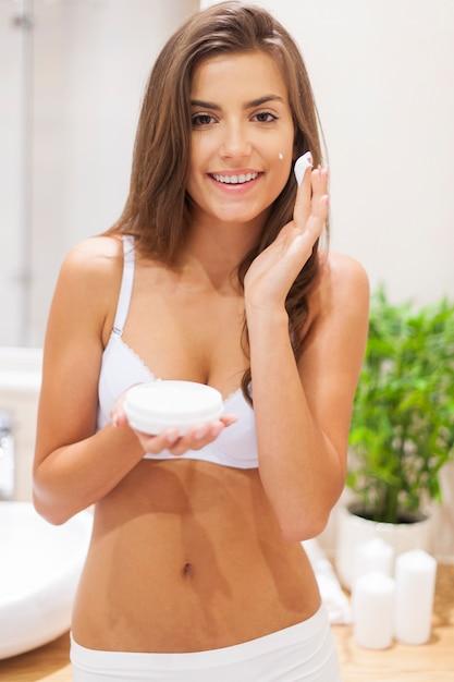 Schoonheid vrouw hydrateert de huid in de badkamer Gratis Foto