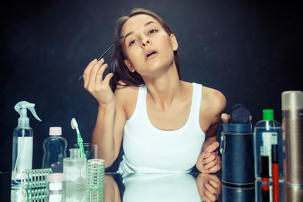 Schoonheid vrouw make-up toe te passen. mooi meisje in de spiegel kijken en cosmetica met een borstel toe te passen. ochtend, make-up en menselijke emoties concept. kaukasisch model in de studio Gratis Foto