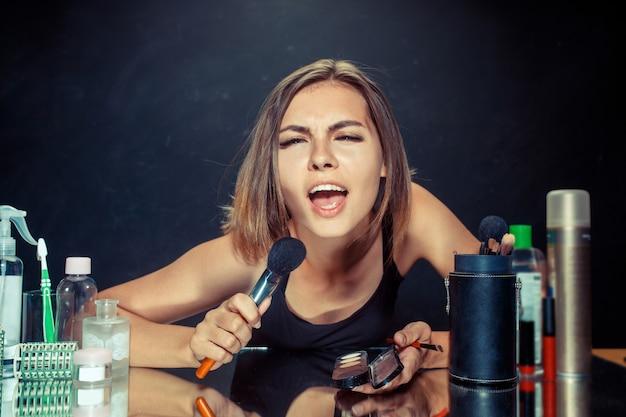 Schoonheid vrouw make-up toe te passen. mooi meisje in de spiegel kijken en cosmetica met een grote borstel toe te passen. kaukasisch model bij studio zingen lied Gratis Foto