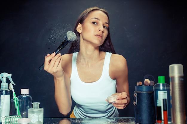 Schoonheid vrouw make-up toe te passen. mooi meisje in de spiegel kijken en cosmetica met een grote borstel toe te passen. kaukasisch model in de studio Gratis Foto