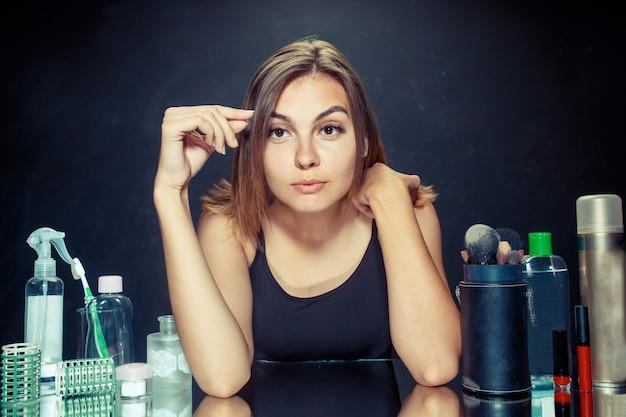 Schoonheid vrouw make-up toe te passen. mooi meisje in de spiegel kijken en cosmetica met een grote borstel toe te passen. Gratis Foto
