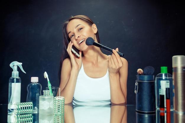 Schoonheid vrouw met mobiele telefoon make-up toe te passen. mooi meisje in de spiegel kijken en cosmetica met een grote borstel toe te passen. kaukasisch model in de studio Gratis Foto