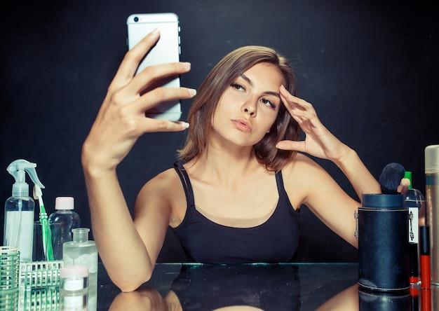 Schoonheid vrouw na het toepassen van make-up. schoonheid vrouw met make-up. mooi meisje kijken naar de mobiele telefoon en selfie foto maken. kaukasisch model in de studio Gratis Foto