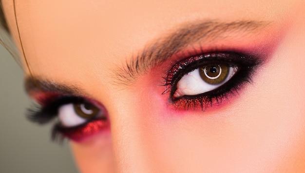 Schoonheid vrouw ogen. mooie vrouw met perfecte wimpers. vrouwelijk schoonheidsgezichtsconcept voor ogen. een professionele visagist schildert ogen in de studio Premium Foto