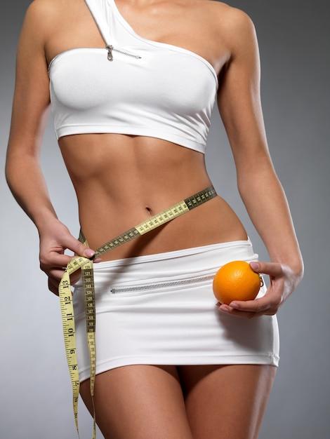 Schoonheid vrouwelijk lichaam met meetlint en sinaasappel. gezonde levensstijl cocnept. Gratis Foto