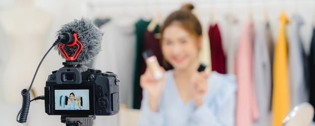 Schoonheids blogger huidig schoonheidsmiddelen die opnamevideocamera zitten Gratis Foto