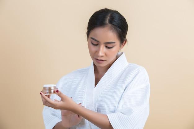 Schoonheidsbehandeling met vrouw houdt een vochtinbrengende crème in haar hand Gratis Foto
