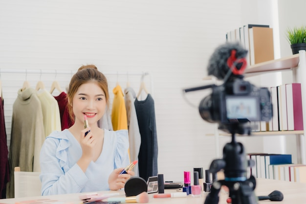 Schoonheidsblogger huidig schoonheidsschoonheidsmiddelen terwijl het zitten vooraan camera voor het registreren van video Gratis Foto