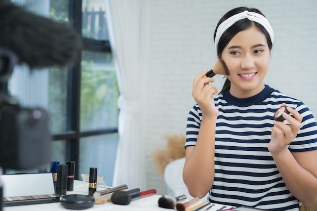 Schoonheidsblogger huidig schoonheidsschoonheidsmiddelen terwijl het zitten vooraan camera voor opnamevideo Gratis Foto