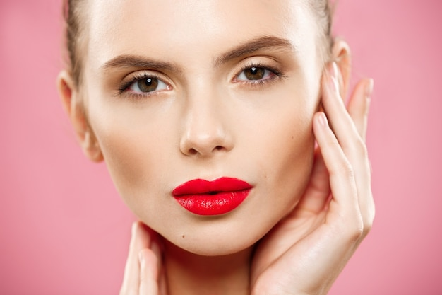 Schoonheidsconcept - close-up gorgeous young brunette woman face portrait. beauty model meisje met lichte wenkbrauwen, perfecte make-up, rode lippen, aanraken van haar gezicht. geïsoleerd op roze achtergrond Gratis Foto