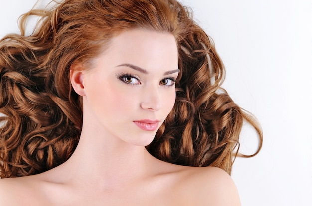 Schoonheidsgezicht van de aantrekkelijke jonge vrouw met krullende haren Gratis Foto