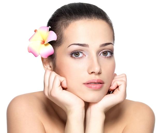Schoonheidsgezicht van jonge vrouw met bloem. schoonheidsbehandeling concept. portret over witte achtergrond Gratis Foto
