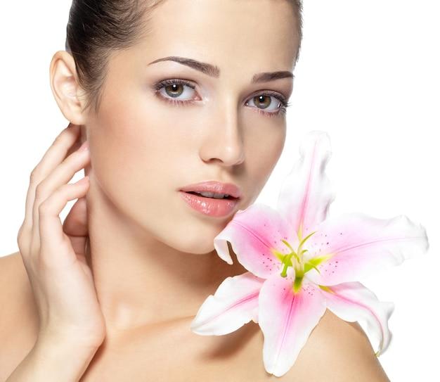 Schoonheidsgezicht van jonge vrouw met bloem. schoonheidsbehandeling concept. portret over witte muur Gratis Foto