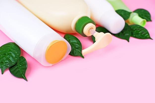 Schoonheidsmiddelen voor haar en lichaamsverzorging witte flessen op een roze achtergrond Premium Foto