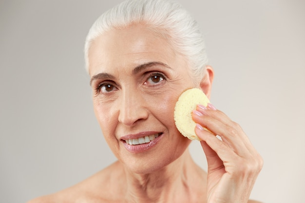Schoonheidsportret van een glimlachende half naakte bejaarde die samenstellingsspons gebruiken bij haar gezicht en camera bekijken Gratis Foto