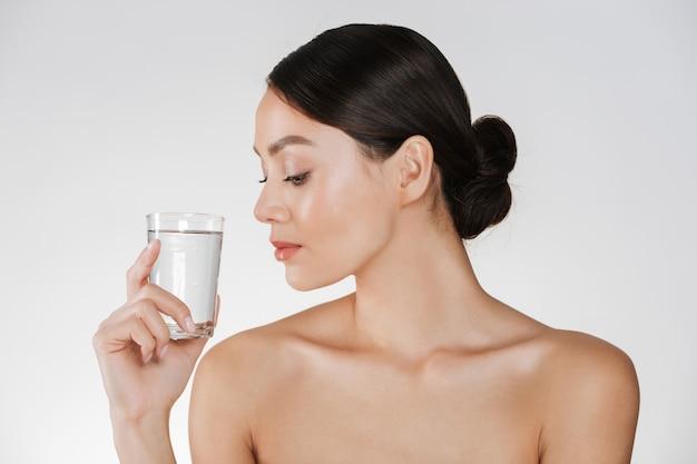 Schoonheidsportret van jonge gelukkige vrouw met haar in broodje die transparant glas van nog water bekijken die ter beschikking houden, dat over wit wordt geïsoleerd Gratis Foto