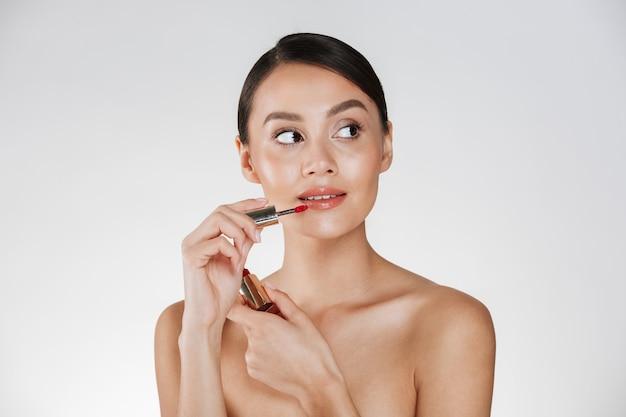 Schoonheidsportret van prachtige vrouw met gezonde huid die rode lipgloss toepast en weg kijkt, geïsoleerd over wit Gratis Foto