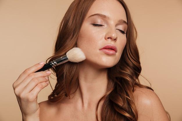 Schoonheidsportret van sensuele gembervrouw met lang haar en gesloten ogen die schoonheidsmiddelen met borstel toepassen Gratis Foto