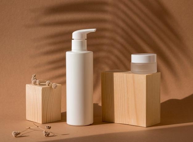 Schoonheidsproducten in verschillende recipiënten arrangement met houten blokken Premium Foto