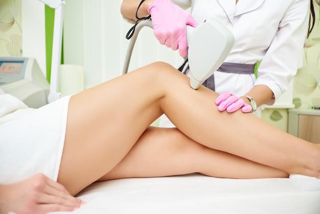 Schoonheidssalon, laser ontharing, arts en patiënt Premium Foto
