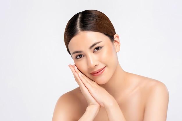 Schoonheidsschot van jeugdige heldere huid vrij aziatische vrouw met handen wat betreft gezicht Premium Foto