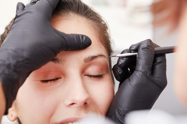 Schoonheidsspecialist brengt permanente make-up aan op wenkbrauwen Premium Foto