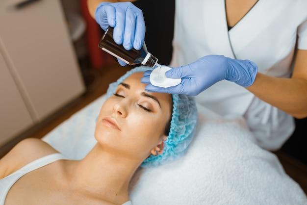 Schoonheidsspecialist en vrouwelijke patiënt, gezichtshuid reinigen. verjongingsprocedure in schoonheidsspecialiste salon. Premium Foto