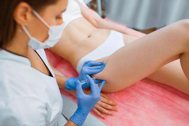 Schoonheidsspecialist in handschoenen geeft botox injectie in de dij aan vrouwelijke patiënt op behandeltafel. verjongingsprocedure in schoonheidsspecialiste salon. Premium Foto