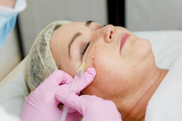 Schoonheidsspecialiste die gezichtsinjectie voor vrouw doet. cosmetische procedure voor revitalisering tegen veroudering Premium Foto