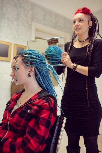 Schoonheidsspecialiste die het haar van klanten stylt Gratis Foto