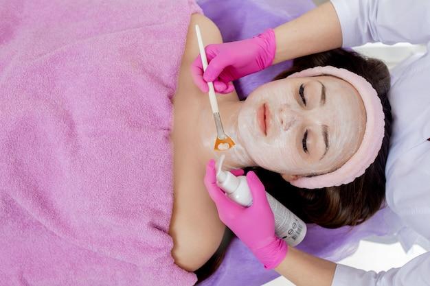 Vrouw die haar gezicht met een masker | Gratis Foto