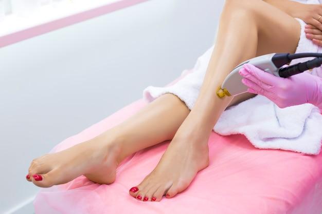 Schoonheidsspecialiste maakt laser ontharing op de mooie en slanke benen van een meisje in een kliniek. Premium Foto